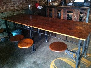 Industrial Table With 8 Swinging Stool Attached photo