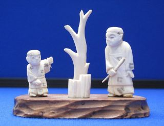 Antique Japanese Carved Ox Bone Father & Son Netsuke Okimono On Wood Stand photo