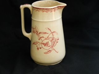 Antique Pottery Pitcher With Bird,  Butterfly,  And Plant Design photo