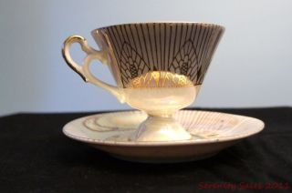 Vintage Porcelain Cup And Saucer Set With Iridescent Glaze And Gold Markings photo