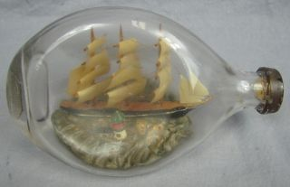 Antique Folk Art Sailing Ship In A Pinched Bottle Lighthouse In Foreground photo