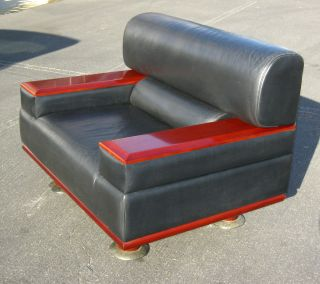 Vintage Contemporary Black Leather Lounging Chair Red Wood Panel Armrests photo