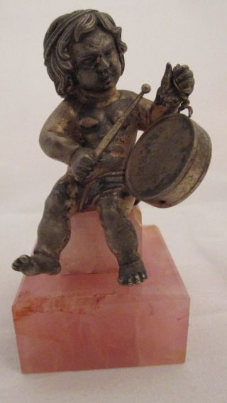 Silver And Rose Quartz Young Child Playing On A Drum photo