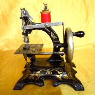 Antique Victorian Cast Iron Small Toy Sewing Machine With Golden Decorations. photo